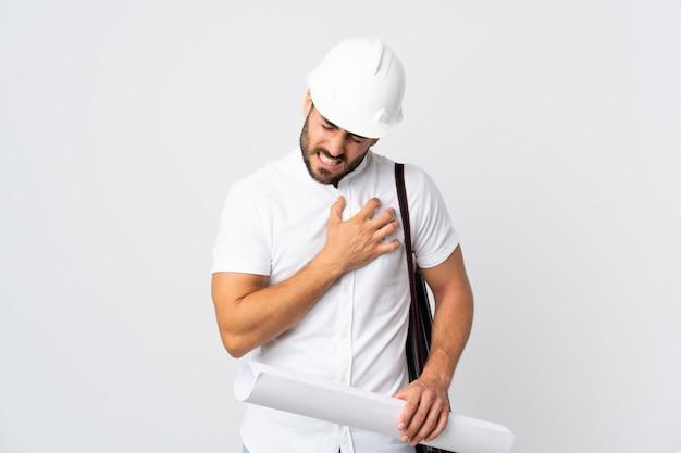 Jonge architectenmens met helm en blauwdrukken houden die op witte muur worden geïsoleerd die pijn in het hart heeft