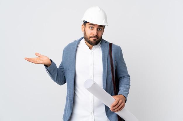 Jonge architectenmens met helm en blauwdrukken houden die op witte muur worden geïsoleerd die twijfels hebben terwijl het opheffen van handen
