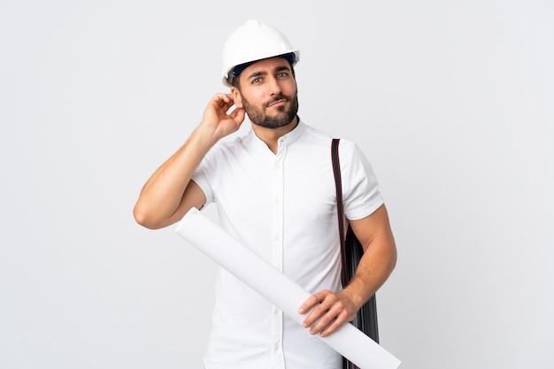 Jonge architectenmens met helm en blauwdrukken houden die op witte muur worden geïsoleerd die twijfels heeft