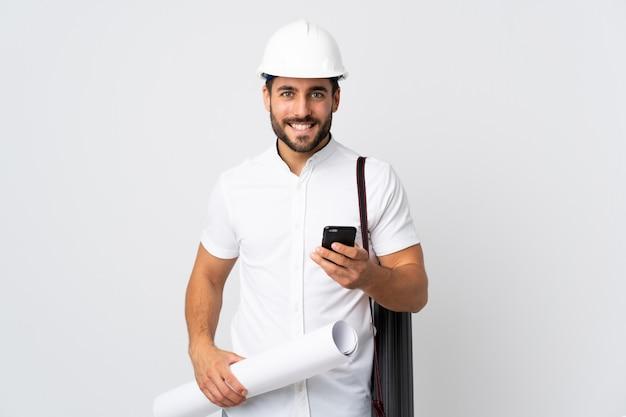 Jonge architectenmens met helm en blauwdrukken op witte muur houden die een bericht met mobiel verzenden