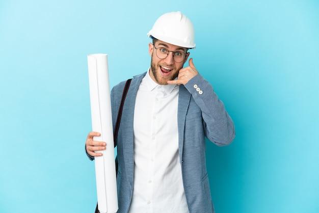 Jonge architectenmens met helm en blauwdrukken over geïsoleerd houden die telefoongebaar maken