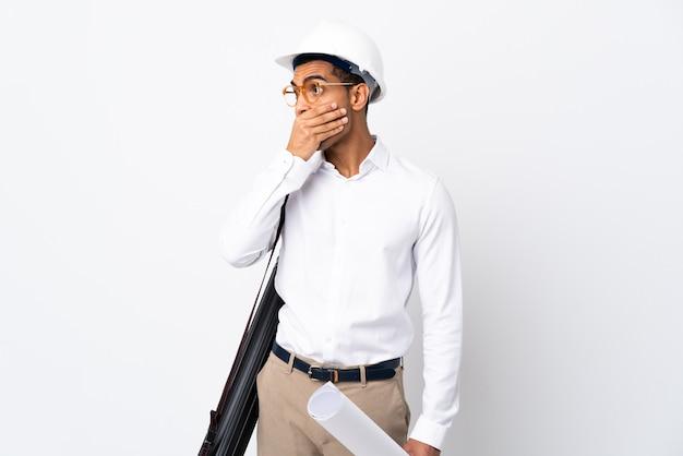 Jonge architectenmens met helm en blauwdrukken over geïsoleerde witte muur die mond bedekken en naar de zijkant kijken