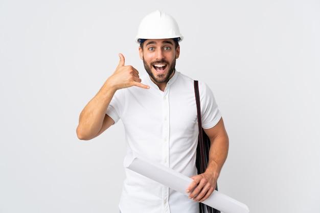 Jonge architectenmens met helm en holdingsblauwdrukken die op wit wordt geïsoleerd dat telefoongebaar maakt. bel me terug teken