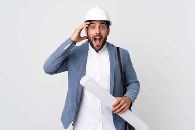 Jonge architectenmens met helm en holdingsblauwdrukken die op witte muur met verrassingsuitdrukking wordt geïsoleerd
