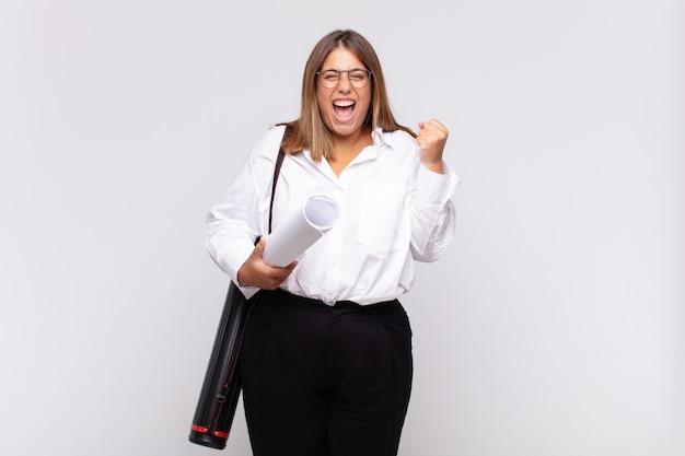 Jonge architectenvrouw die agressief met een boze uitdrukking of met gebalde vuisten schreeuwen het vieren van succes