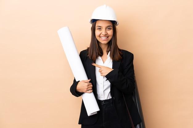 Jonge architectenvrouw die blauwdrukken over geïsoleerde muur houdt die naar de kant richten om een product te presenteren