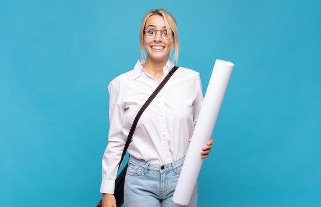 Jonge architectenvrouw die er blij en aangenaam verrast uitzag, opgewonden met een gefascineerde en geschokte uitdrukking