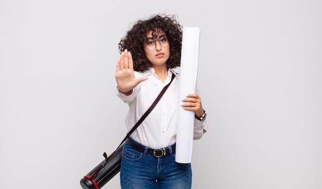 Jonge architectenvrouw die ernstig, streng, ontevreden en boos kijkt die open palm toont die stopgebaar maakt