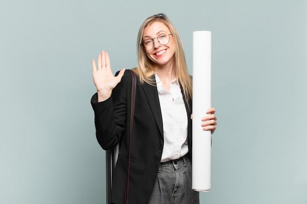Jonge architectenvrouw die gelukkig en opgewekt glimlacht, met de hand zwaait, u verwelkomt en begroet, of afscheid neemt
