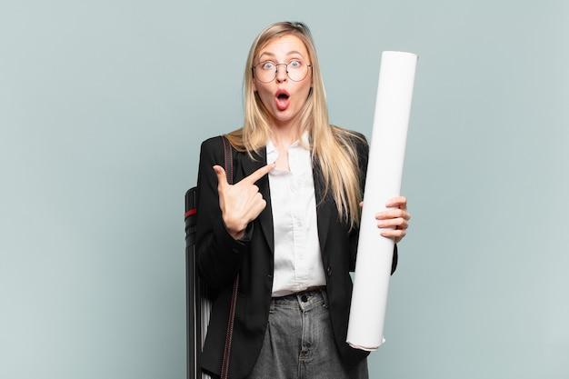 Jonge architectenvrouw die geschokt en verrast kijkt met wijd open mond, wijzend naar zichzelf