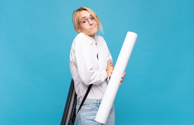 Jonge architectenvrouw die haar schouders ophaalt, zich verward en onzeker voelt, twijfelt met gekruiste armen en verbaasde blik