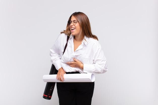 Jonge architectenvrouw die hardop lacht om een hilarische grap, zich gelukkig en opgewekt voelt, plezier heeft
