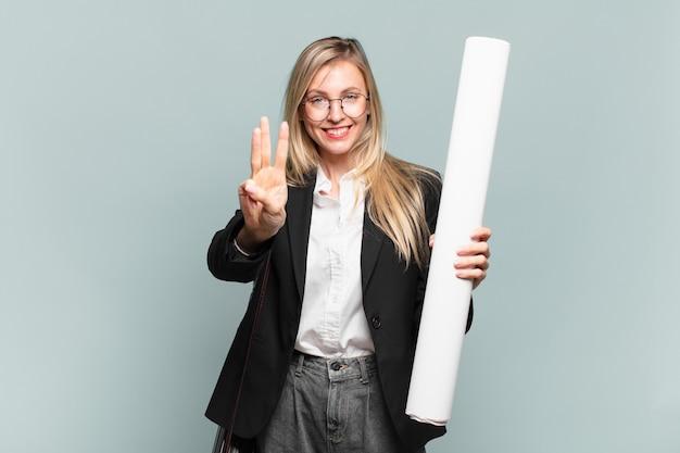 Jonge architectenvrouw die lacht en er vriendelijk uitziet, nummer drie of derde toont met de hand naar voren, aftellend