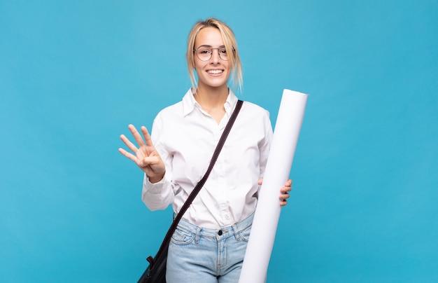 Jonge architectenvrouw die lacht en er vriendelijk uitziet, nummer vier of vierde toont met de hand naar voren, aftellend