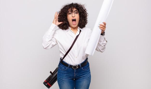 Jonge architectenvrouw die met handen in de lucht schreeuwt, woedend, gefrustreerd, gestrest en boos voelt