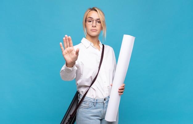Jonge architectenvrouw die serieus, streng, ontevreden en boos kijkt en een open palm toont die een stopgebaar maakt