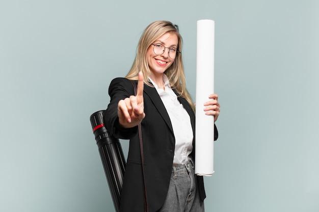 Jonge architectenvrouw die trots en zelfverzekerd glimlacht en nummer één triomfantelijk poseert, voelt zich een leider