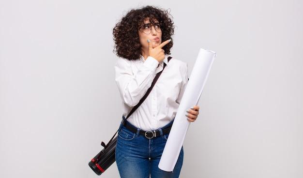 Jonge architectenvrouw die, twijfelachtig en verward denkt, met verschillende opties denkt, zich afvraagt welke beslissing te nemen