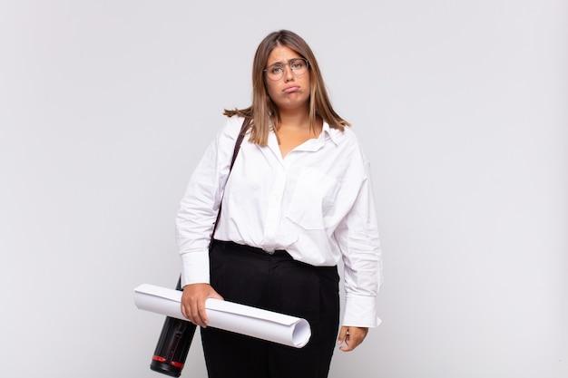 Jonge architectenvrouw die verdrietig en zeurderig is met een ongelukkige blik, huilend met een negatieve en gefrustreerde houding