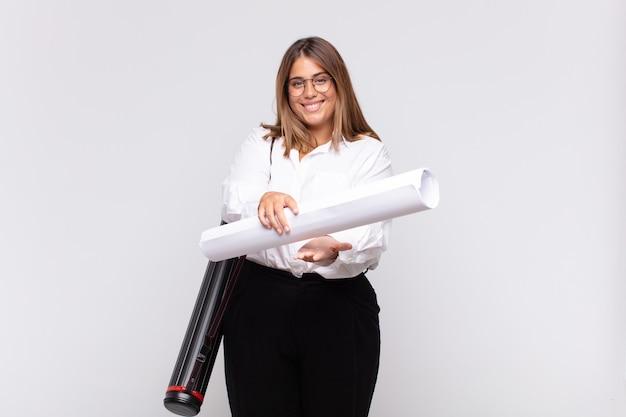 Jonge architectenvrouw die vrolijk lacht met een vriendelijke, zelfverzekerde, positieve blik, een object of concept aanbiedt en toont
