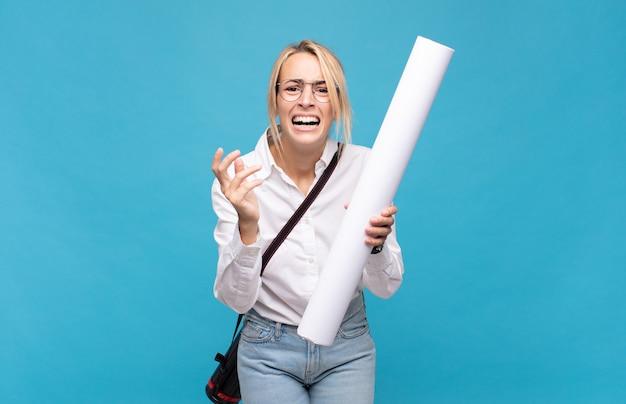 Jonge architectenvrouw die wanhopig en gefrustreerd, gestrest, ongelukkig en geïrriteerd kijkt, schreeuwt en schreeuwt