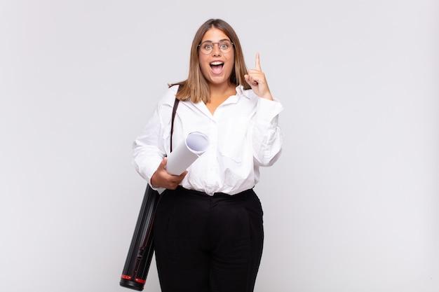 Jonge architectenvrouw die zich als een gelukkig en opgewonden genie voelt na het realiseren van een idee, vrolijk de vinger opheffend, eureka!