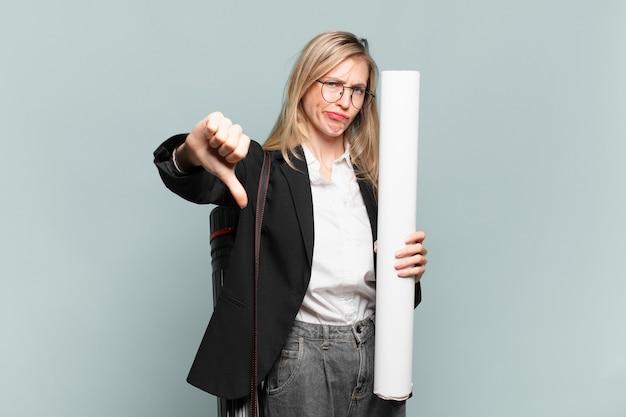 Jonge architectenvrouw die zich boos, boos, geïrriteerd, teleurgesteld of ontevreden voelt, duimen naar beneden met een serieuze blik