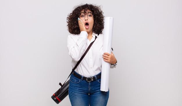 Jonge architectenvrouw die zich geschokt en bang voelt, doodsbang kijkt met open mond en handen op de wangen