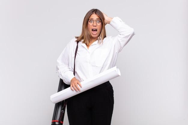 Jonge architectenvrouw die zich gestrest, bezorgd, angstig of bang voelt, met de handen op het hoofd, in paniek raakt bij vergissing