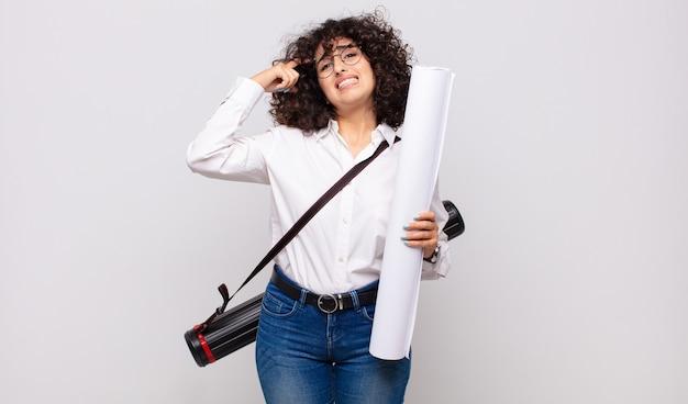 Jonge architectenvrouw die zich verward en verbaasd voelt, laat zien dat je gek, gek of gek bent