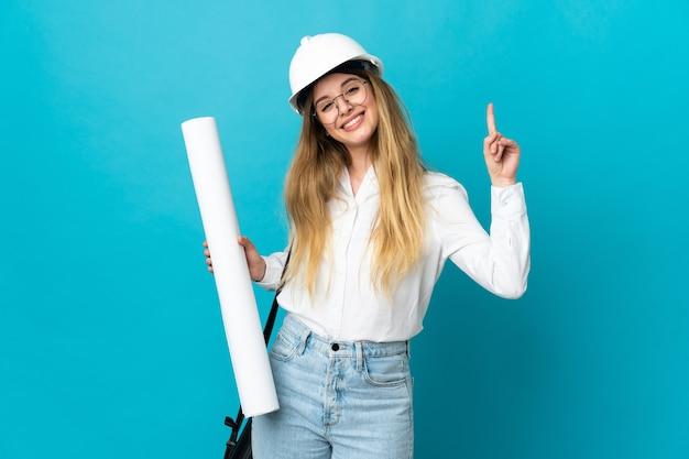 Jonge architectenvrouw met helm en blauwdrukken houden die op blauwe muur worden geïsoleerd die en een vinger opheffen als teken van het beste