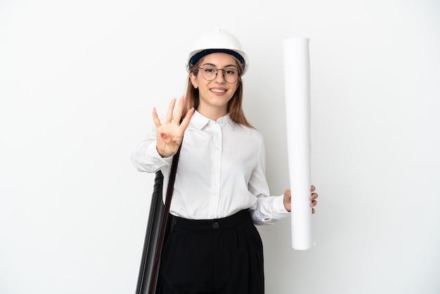 Jonge architectenvrouw met helm en blauwdrukken houden die op witte muur gelukkig worden geïsoleerd en vier met vingers tellen