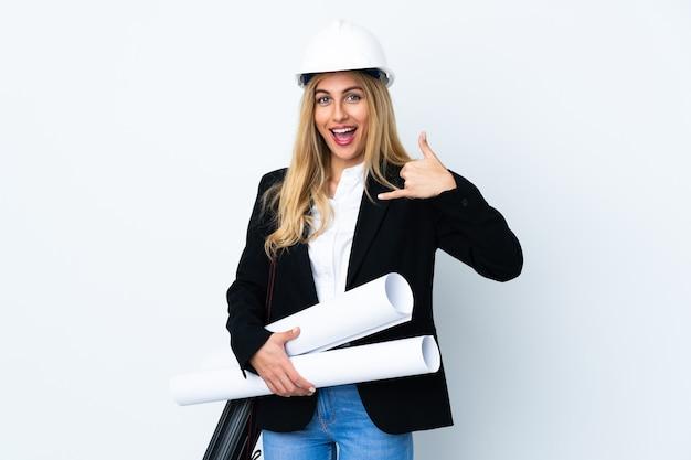 Jonge architectenvrouw met helm en blauwdrukken houden over geïsoleerde witte muur die telefoongebaar maken