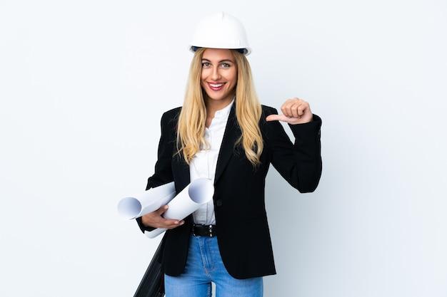 Jonge architectenvrouw met helm en blauwdrukken houden over geïsoleerde witte muur trots en zelfvoldaan