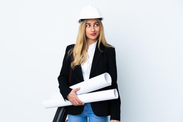 Jonge architectenvrouw met helm en blauwdrukken houden over geïsoleerde witte ruimte die en zich aan de kant bevinden kijken