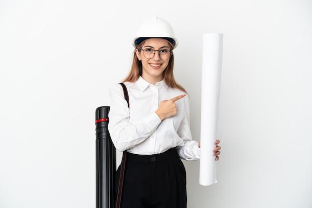 Jonge architectenvrouw met helm en blauwdrukken op wit houden die naar de kant wijzen om een product te presenteren