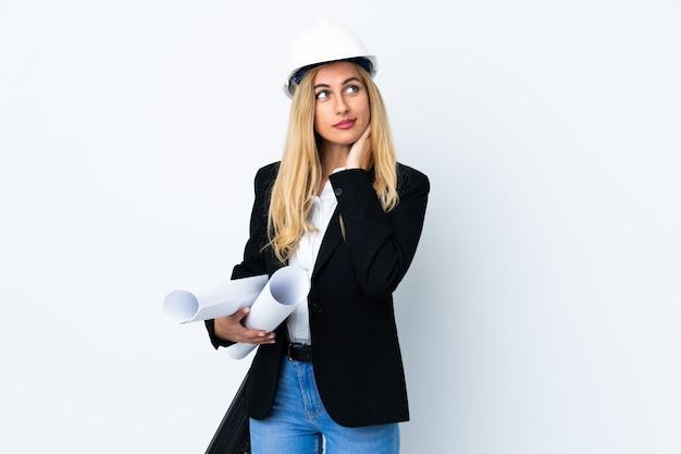 Jonge architectenvrouw met helm en blauwdrukken over geïsoleerde witte ruimte houden die een idee denken