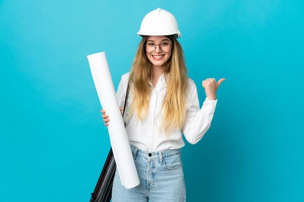 Jonge architectenvrouw met helm en holdingsblauwdrukken die op blauwe muur worden geïsoleerd die naar de kant richten om een product te presenteren