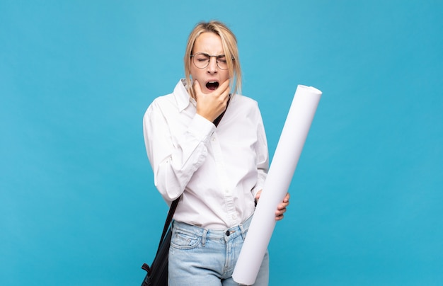 Jonge architectenvrouw met mond en ogen wijd open en hand op kin, onaangenaam geschokt, zeggend wat of wauw