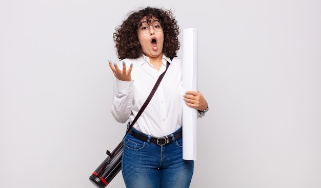 Jonge architectenvrouw met open mond en verbaasd, geschokt en verbaasd over een ongelooflijke verrassing