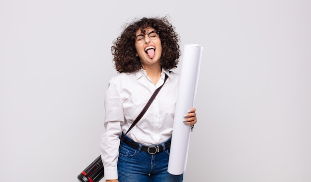 Jonge architectenvrouw met vrolijke, zorgeloze, rebelse houding, grappen maken en tong uitsteken, plezier maken