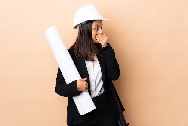 Jonge architectvrouw die blauwdrukken over geïsoleerde muur behandelt die mond houdt en naar de kant kijkt