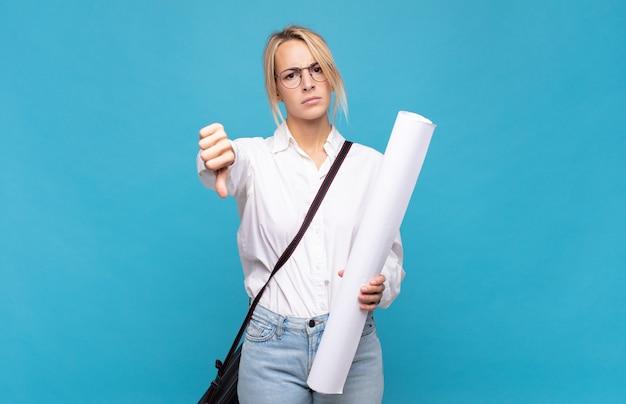 Jonge architectvrouw die zich boos, boos, geïrriteerd, teleurgesteld of ontevreden voelt, duimen naar beneden toont met een serieuze blik