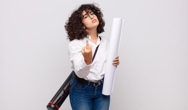 Jonge architectvrouw die zich boos, geërgerd, opstandig en agressief voelt, de middelvinger wegknipt, terugvecht