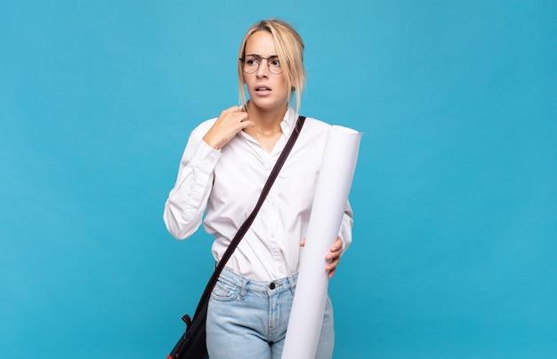 Jonge architectvrouw die zich gestrest, angstig, moe en gefrustreerd voelt, de hals van het shirt trekt, gefrustreerd kijkt door het probleem