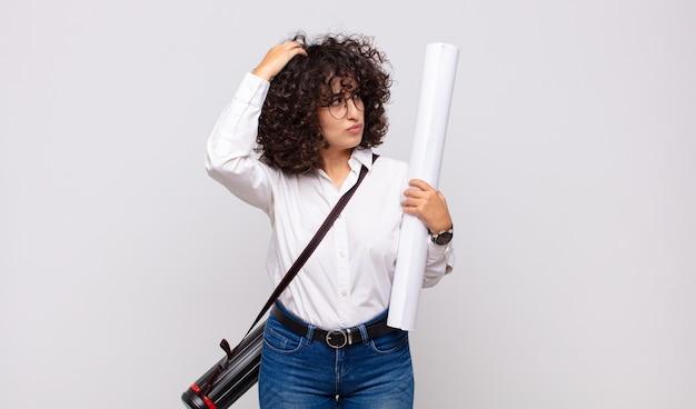 Jonge architectvrouw die zich in verwarring en verward voelt, hoofd krabt en naar de zijkant kijkt