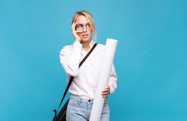 Jonge architectvrouw die zich verveeld, gefrustreerd en slaperig voelt na een vermoeiende, saaie en vervelende taak, gezicht met de hand vasthouden