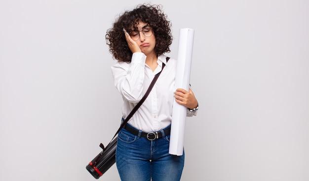 Jonge architectvrouw die zich verveeld, gefrustreerd en slaperig voelt na een vermoeiende, saaie en vervelende taak, gezicht met hand vasthoudend