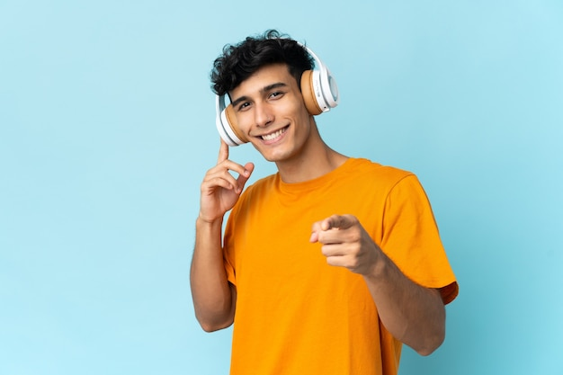 Jonge argentijnse man die op muur luisterende muziek en naar voren wijst