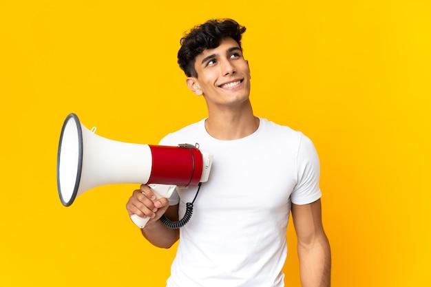Jonge argentijnse man geïsoleerd op een gele achtergrond die een megafoon vasthoudt en omhoog kijkt terwijl hij glimlacht